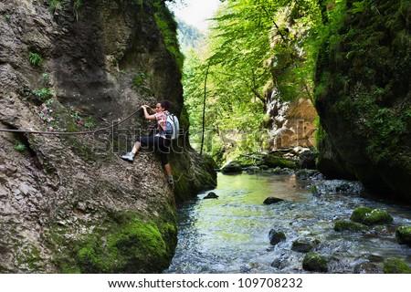 Woman climbing mountain wall over a river in a canyon - stock photo