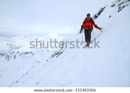 Woman climbing the mountain in bad weather during winter
