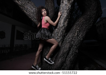 Woman climbing the tree to getaway from the bad guys