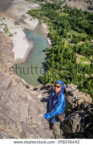 Woman climbing to the top of a rock hill in the middle of the beautiful green and fertile mountain valley in the Karakorum mountains in Pakistan, Skardu region - stock photo