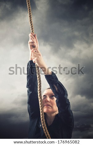 Woman climbing up with rope. Overcoming problems, obstacles and difficulties in life metaphor. - stock photo