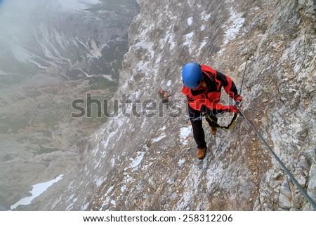 "Woman climbs high on rock wall while snow spots cover the route of via ferrata ""Lipella"", Tofana massif, Dolomite Alps, Italy - stock photo"