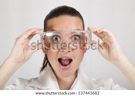 Woman closeup portrait of young doctor, surgeon or nurse, looking surprised starring with big eyes wearing protective glasses