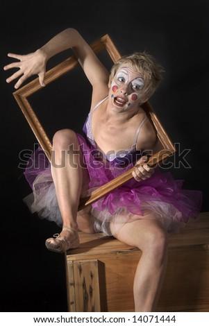 Woman clown climbing through an empty picture frame - stock photo