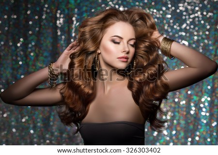 Woman club lights party background Dancing girl Long hair. Waves Curls Updo Hairstyle. Hair Salon Fashion model with shiny  healthy hair with luxurious haircut. Hair volume Jewelry Bracelets Earrings