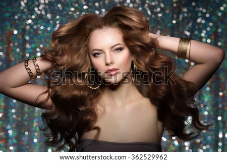 Woman club lights party background Dancing girl Long hair. Waves Curls Updo Hairstyle. Hair Salon Fashion model with shiny healthy hair with luxurious haircut. Hair volume Jewelry Bracelets Earrings - stock photo