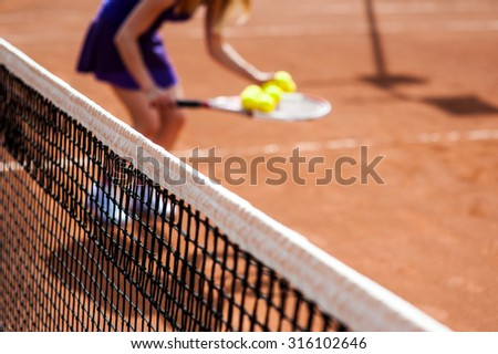 Woman collects tennis balls and preparing for sports competition. Professional athlete in a form proves the equality of women over men. - stock photo