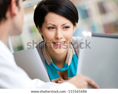 Woman communicates with man showing her something in the tablet sitting at the table at the reading hall - stock photo