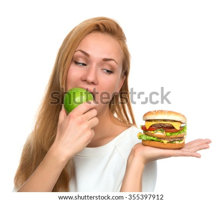 Woman compare tasty unhealthy burger sandwich in hand and green apple getting ready to eat isolated on a white background healthy eating concept - stock photo