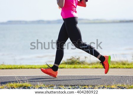 Woman compete in the marathon race on coastal road