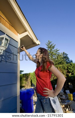 Woman concentrates as she paints her house. Vertically framed photograph. - stock photo