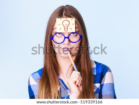 Woman confused thinking seeks solution, paper card with light idea bulb on her head. Girl is trying to create a new idea for some business project or case study studio shot on blue