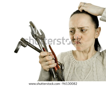 woman confused which tool to use on white background - stock photo