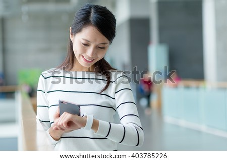Woman connect cellphone and smart watch - stock photo