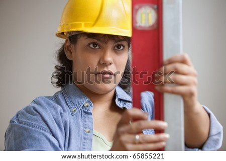 Woman construction worker in hard hat reading level measurements - stock photo