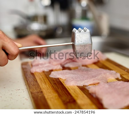 Woman cook beating turkey breast fillets with meat tenderizer