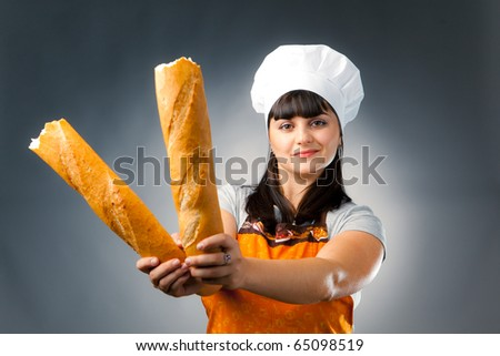 woman cook holding breaked french bread - stock photo