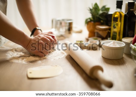 Woman cooking in the kitchen.Healthy food and lifestyle.Eating in.Cooking at home.Prepare dough for homemade whole grain bread.Woman kneading dough with her hands.Carbohydrates.Dieting Concept. - stock photo