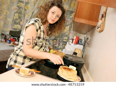 woman cooking pancakes at kitchen - stock photo