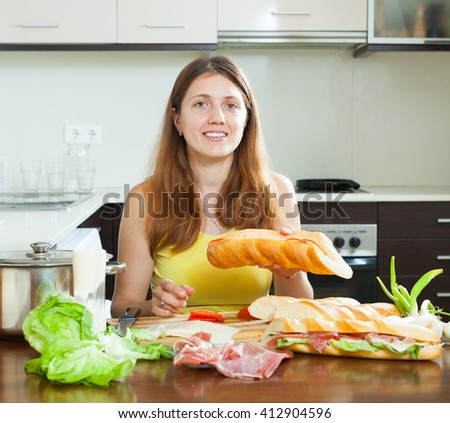 woman cooking spanish sandwiches (bocadillo) with vegetables and  hamon in home kitchen
