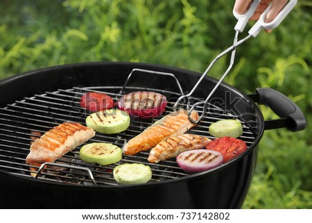 Woman cooking tasty salmon slices with vegetables on barbecue grill outdoors
