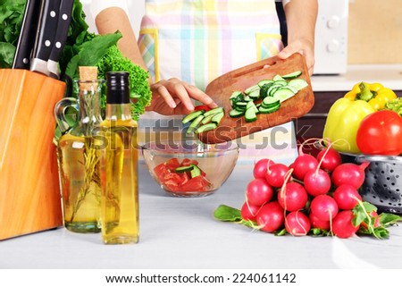 Woman cooking vegetable salad in kitchen - stock photo