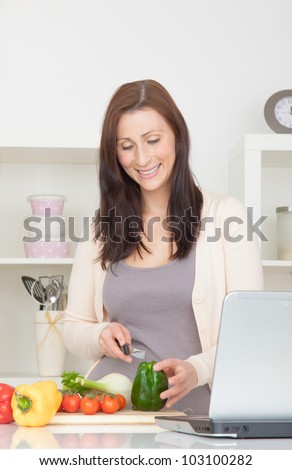 woman cooking with notebook computer recipe