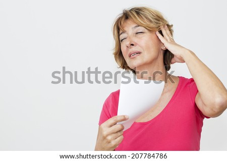Woman cooling herself with a  blank paper. - stock photo