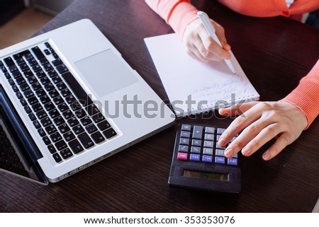 Woman counting on calculator sitting at the table. Close up view of hands and stationery