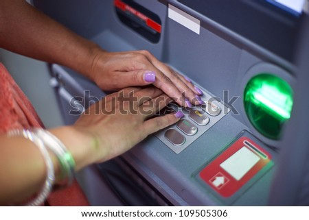 woman covering atm machine keypad with her hands and entering her pin number - stock photo