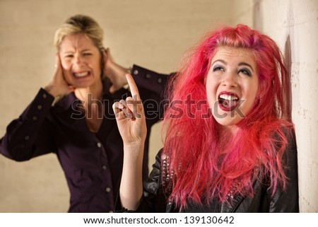 Woman covering ears while woman in pink hair sings - stock photo
