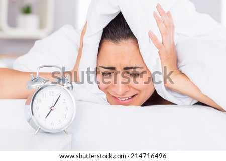 Woman covering ears with sheet in bed and alarm clock on side table - stock photo