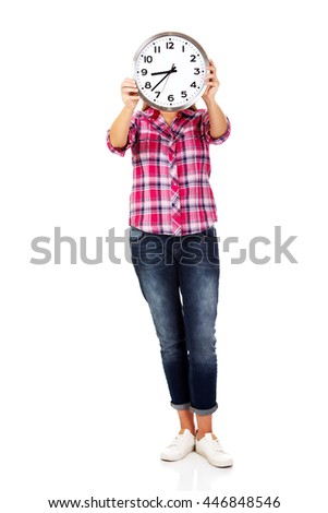 Woman covering face with a clock - stock photo