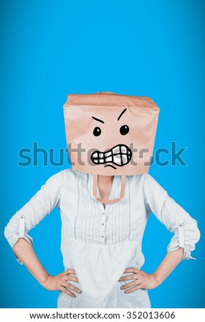 Woman covering head with brown paper bag against blue background with vignette - stock photo