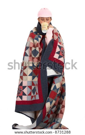 woman covering her body with quilt while sipping a coffee - looking very cold - stock photo