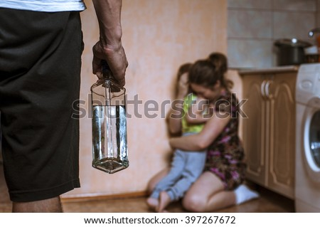 Woman covering her child from angry drunk father. Domestic violence. - stock photo