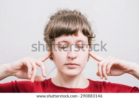 Woman covering her ears. On a gray background.