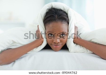 Woman covering her ears with a duvet in her bedroom