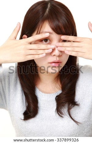 woman covering her face with hands peeping at the camera through her fingers - stock photo