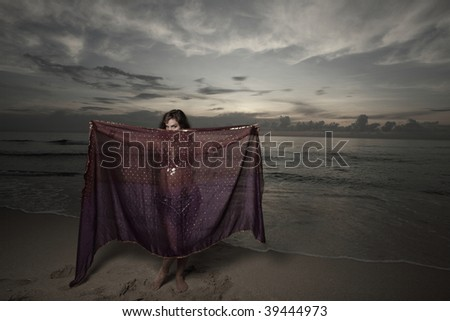 Woman covering her self with a purple veil - stock photo