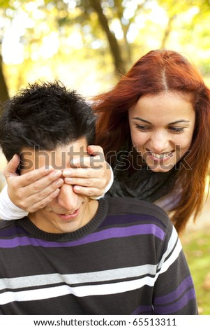 woman covering the eyes to his boyfriend (selective focus with shallow DOF) - stock photo