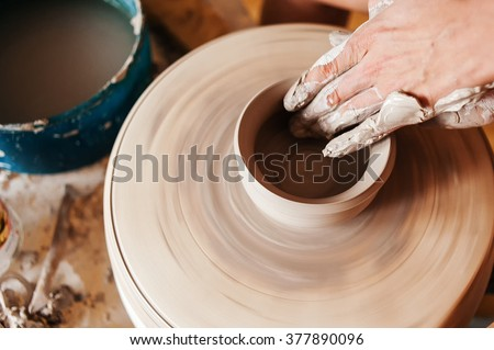 Woman creating a clay jar on a potter's wheel - stock photo