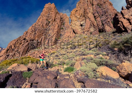 Woman cross country running in mountains on dirt path. Beauty female runner jogging and training with backpack outdoors in nature, trail running on rocky trail footpath on Tenerife, Canary Islands. - stock photo