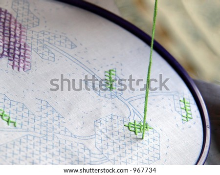 Woman Cross Stitching green and purple flower for a quilt - stock photo