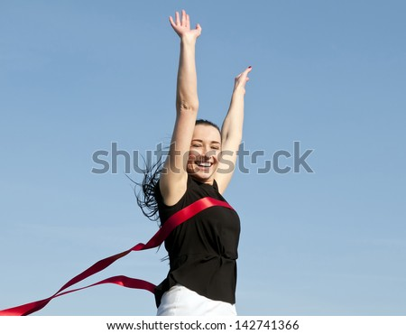 woman crossing finishing line - stock photo