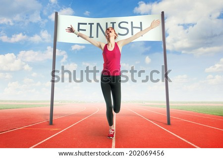 Woman crossing the finish line - stock photo