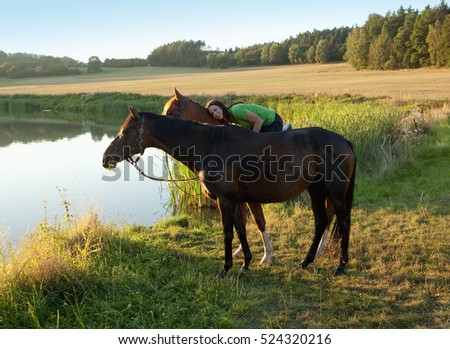 Woman Cuddles with Two Horses by a Lake