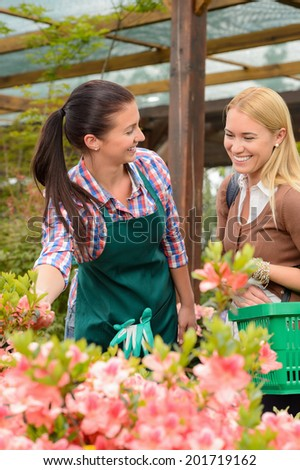 Woman customer talking to worker about plants in garden center - stock photo