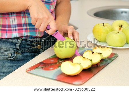 Woman cuts apples - stock photo