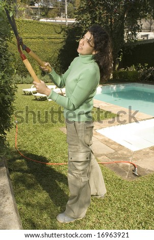 Woman cuts shrubs with trimmers. She is smiling and working in a yard. Vertically framed photo. - stock photo